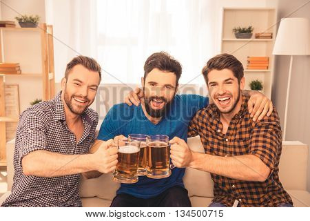 Cheers! Handsome Men Celebrating Victory Of Favorite Team And Clinking Glass Of Beer At Home