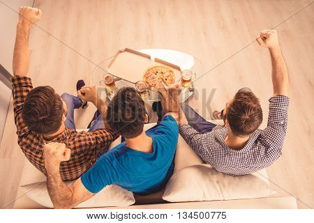 Top-view Photo Of Happy Cheerful Men Resting And Watching Tv