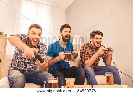 Photo Of Happy Cheerful Men Resting And Play Video Game With Joystick