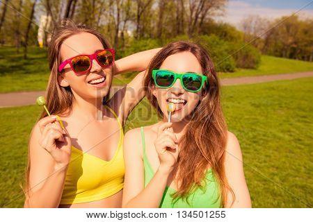 Happy Cheerful Girlfriends In Glasses Licking Chupa Chups