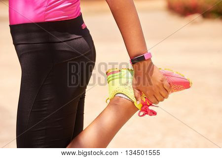 Young people doing sport activities woman runner stretching leg using fit watch. Concept of leisure health recreation fitness lifestyle exercising training workout