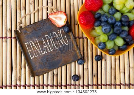 Fresh Seasonal Fruits And A Metal Sign On A Bamboo Mat, German Word