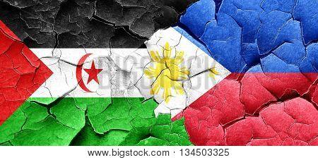 Western sahara flag with Philippines flag on a grunge cracked wa