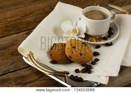 Romantic coffee cup served with white orchid. Morning coffee cup. Cup of strong coffee on the serving tray.