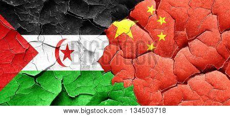 Western sahara flag with China flag on a grunge cracked wall