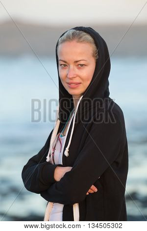 Portrait of casualy dressed active sporty blonde woman on sandy surfers beach at dusk.