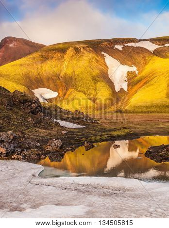 The  sunrise in the Arctic. Light golden dawn illuminates the mountains and glaciers national park Landmannalaugar in Iceland