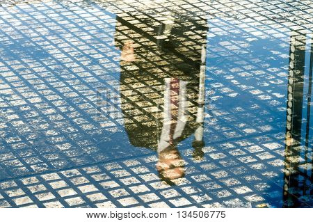 Businessman reflected in a puddle of water on a sidewalk