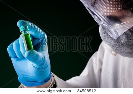 Researcher Examining Green Fluid In A Vial