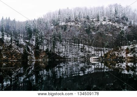 cottage in front a lake in winter (Germany)
