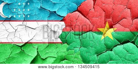 Uzbekistan flag with Burkina Faso flag on a grunge cracked wall