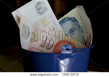 A blue bucket full of Singaporean dollars.