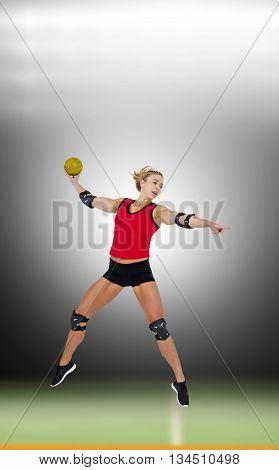 Female athlete with elbow pad throwing handball against digital image of handball field indoor