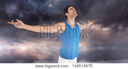 Excited male athlete with arms outstretched against gloomy sky