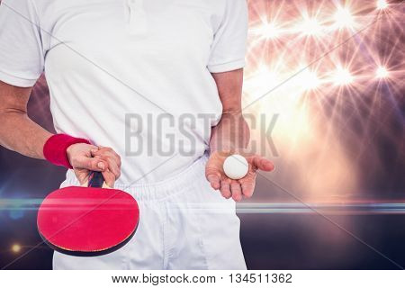 Composite image of male athlete holding ping pong ball and paddle against spotlight