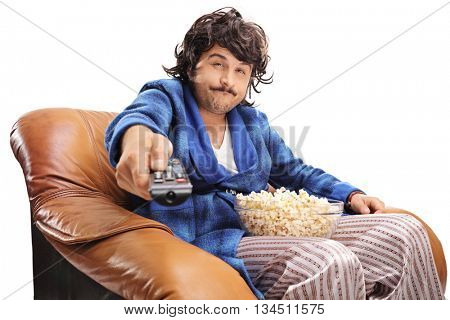 Bored young guy sitting on an armchair and changing the channels on TV isolated on white background