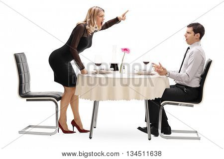 Angry woman yelling at her boyfriend seated at a restaurant table on a date isolated on white background