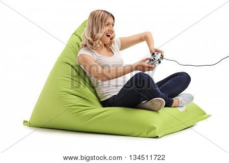 Young joyful woman playing video games seated on a green beanbag isolated on white background