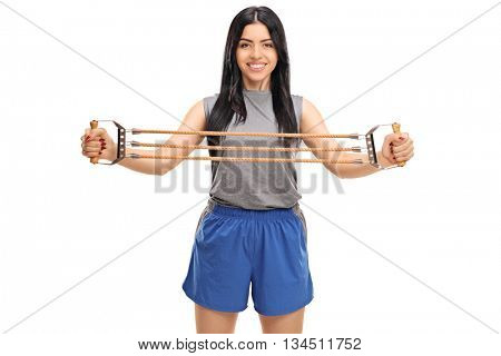 Young woman exercising with a resistance band and looking at the camera isolated on white background