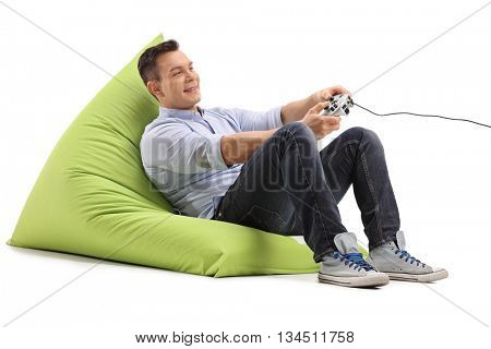Joyful young man playing video games seated on a green beanbag isolated on white background