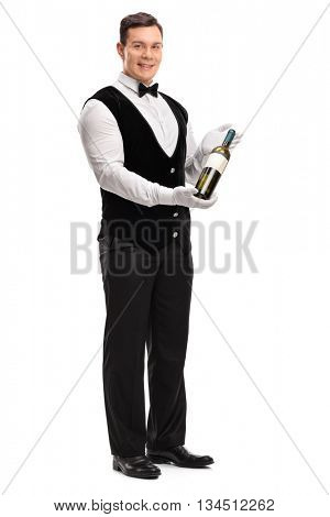 Full length portrait of a professional waiter holding a bottle of white wine isolated on white background