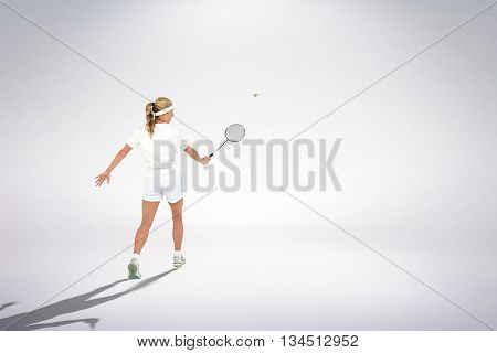 Composite image of badminton player playing badminton against white background