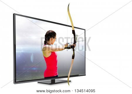 Side view of woman practicing archery against american football arena
