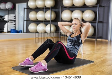 Determined Woman Performing Crunches On Exercise Mat In Gym