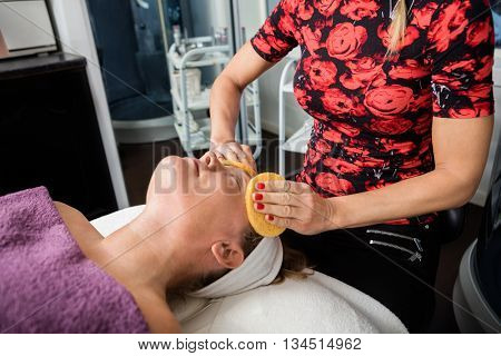 Beautician Cleaning Customer's Face With Sponge