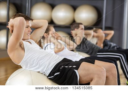Man Doing Crunches With Friends On Ball In Gym