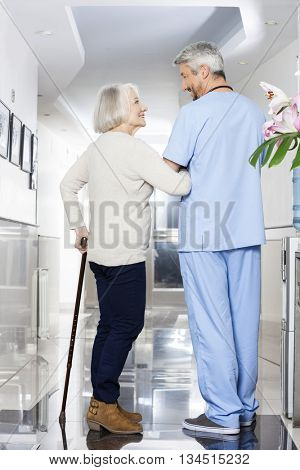 Disabled Senior Woman Holding Cane While Looking At Physiotherap