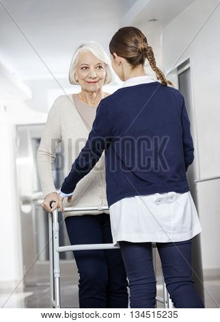 Doctor Helping Senior Patient With Walker In Rehabilitation Cent