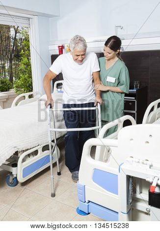 Nurse Helping Male Patient In Using Walker At Rehabilitation Cen