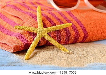 closeup of a yellow starfish on a pile of sand, and a pair of sunglasses on an orange beach towel, placed on a rustic blue wooden surface
