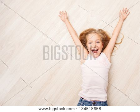 Child lying on floor heating. Girl on laminate, PVC tile