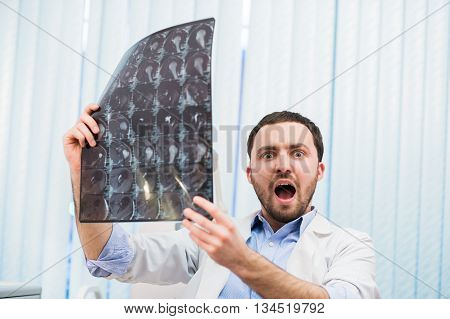 Scared worried doctor reviewing X-ray scan looking at the camera Indoors in office.