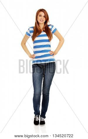 Smiling teenage woman with hands on hips