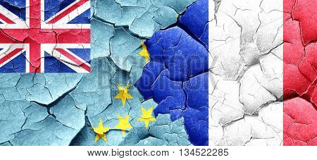 Tuvalu flag with France flag on a grunge cracked wall