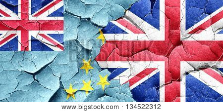 Tuvalu flag with Great Britain flag on a grunge cracked wall