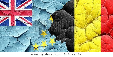 Tuvalu flag with Belgium flag on a grunge cracked wall