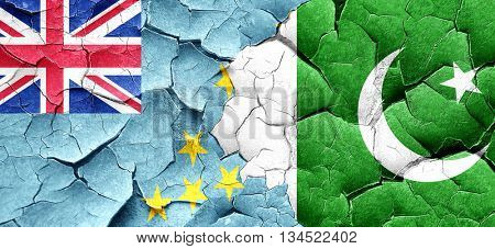 Tuvalu flag with Pakistan flag on a grunge cracked wall