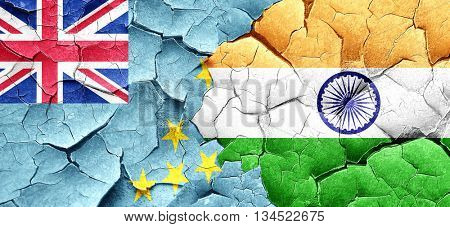 Tuvalu flag with India flag on a grunge cracked wall