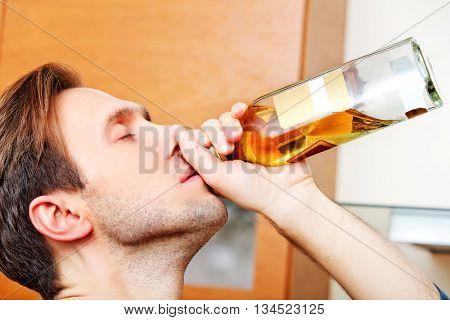Drunken man holding bottle of whiskey