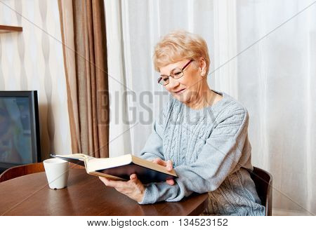 Senior woman sitting at the desk and reading a book and drinking tea
