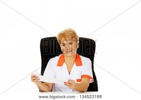 Smile elderly female doctor or nurse sitting behind the desk and holds bandage