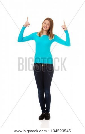 Young woman pointing up with both hands