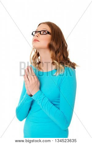 Young sad woman praying holding clasp hands