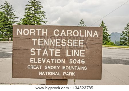 Brown and white sign in Great Smoky Mountains National Park marking the elevation and the North Carolina and Tennessee state lines