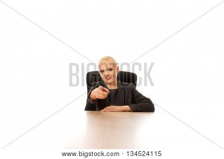 Business woman sitting behind the desk and pointing at camera
