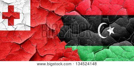 Tonga flag with Libya flag on a grunge cracked wall